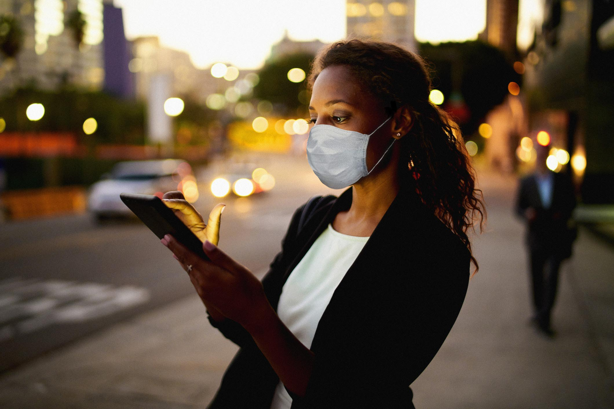 Businesswoman outdoors wearing healthcare mask.